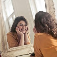 woman looking at image of self in mirror