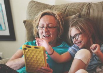 grandmother and granddaughter looking at tablet together