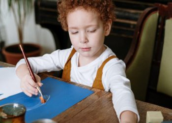 young boy managing emotions by drawing and playing with blocks